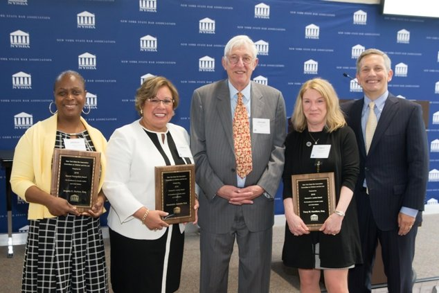 Angela O. Burton, Esq., Hon. Jeanette Ruiz, Hon. Howard A. Levine, Tracy M. Hamilton, Esq., Henry M. Greenberg, Esq., NYSBA President standing in front of blue background, smiling and holding awards.