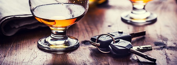 Cup of cognac whiskey or brandy and the keys car.