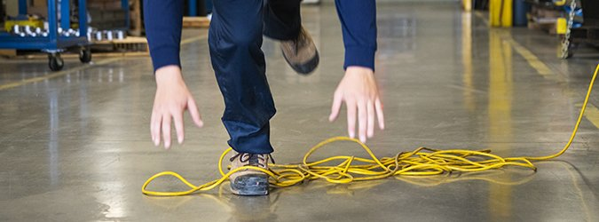 A worker tripping over an electrical cord in an industrial environment