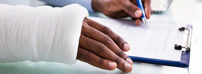 Injured Man Filling Insurance Claim Form