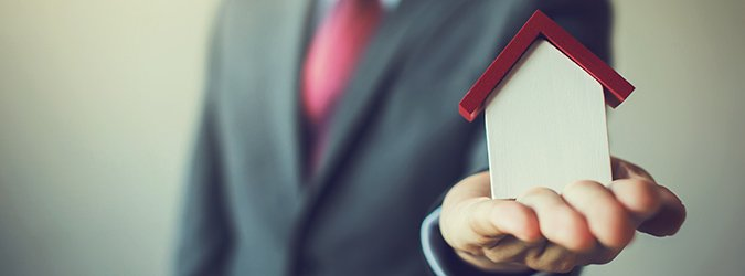 Business man in suit having miniature house on palm hand